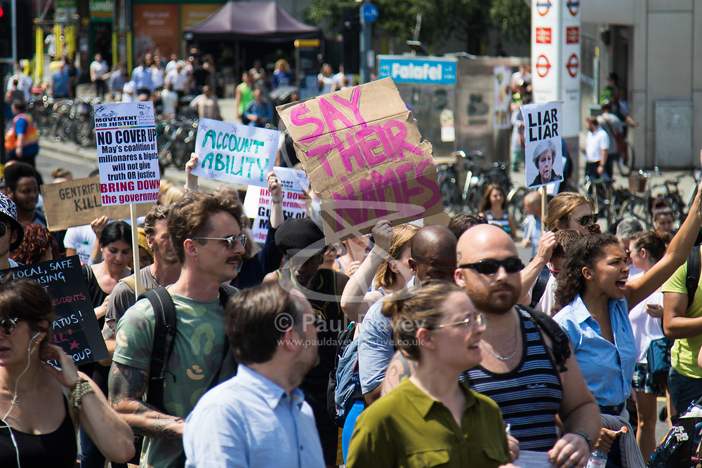 """London, June 21st 2017. Protesters march through London from Sheherd's Bush Green in what the organisers call 'A Day Of Rage' in the wake of the Grenfell Tower fire disaster. The march is organised by the Movement for Justice By Any Means Necessary and coincides with the Queen's Speech at Parliament, the destination. PICTURED: A banner proclaims """"SAY THEIR NAMES"""" as police refuse to release names of victims until confirmed that they were in the tower block."""