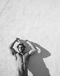 nude muscular man against a white wall