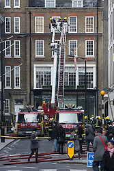 © licensed to London News Pictures. London, UK 04/02/12. Over 100 firefighters are working to bring a fire on Grafton Street in Mayfair, London under control. The fire which started early this morning is in a terrace building that sold for 13million GBP in 2007. Photo credit: Tolga Akmen/LNP