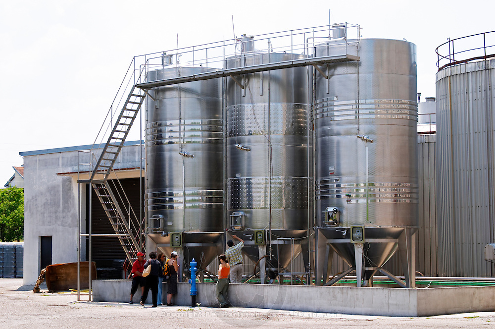 Outside stainless steel fermentation tanks with special design from Italy to allow for the removal of the grape pips after an initial cold maceration and before the main fermentation. Visitors admiring the tanks. Vinarija Citluk winery in Citluk near Mostar, part of Hercegovina Vino, Mostar. Federation Bosne i Hercegovine. Bosnia Herzegovina, Europe.