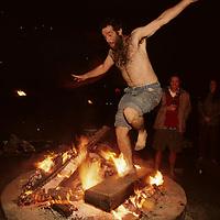 USA, Washington, Seattle, Man leaps through flames of bonfire on beach at Golden Gardens Park on summer evening
