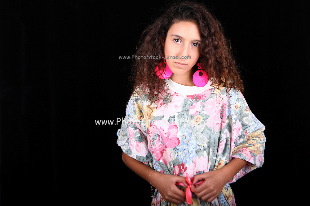 Studio shot of Young teen in floral top on black background