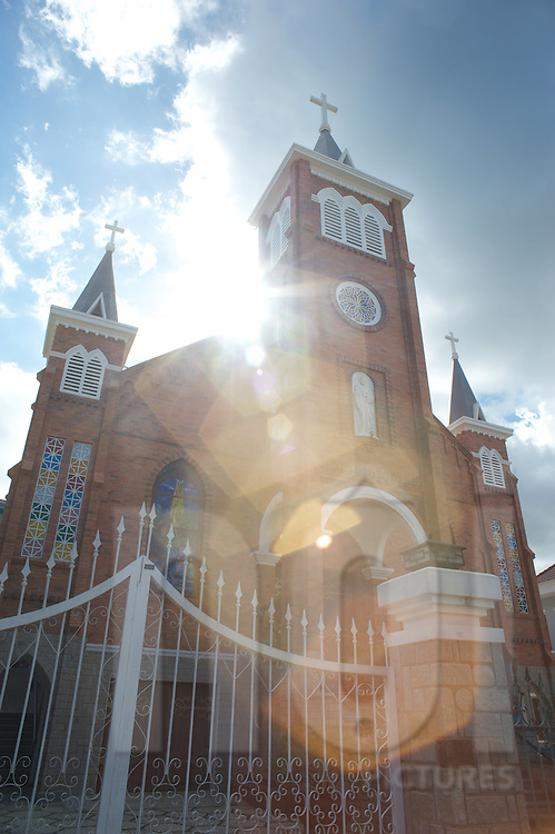 Catholic Church in Dalat, Vietnam, Asia. Picture shows a strong flare due to the sun's backlighting.