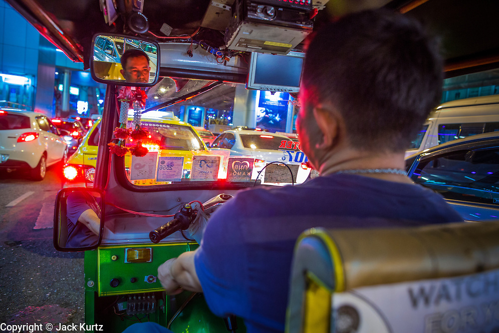 """12 JANUARY 2013 - BANGKOK, THAILAND:  A tuk-tuk driver on Sukhmvit Road between the red light districts of Nana and Soi Cowboy. Prostitution in Thailand is illegal, although in practice it is tolerated and partly regulated. Prostitution is practiced openly throughout the country. The number of prostitutes is difficult to determine, estimates vary widely. Since the Vietnam War, Thailand has gained international notoriety among travelers from many countries as a sex tourism destination. One estimate published in 2003 placed the trade at US$ 4.3 billion per year or about three percent of the Thai economy. It has been suggested that at least 10% of tourist dollars may be spent on the sex trade. According to a 2001 report by the World Health Organisation: """"There are between 150,000 and 200,000 sex workers (in Thailand).""""    PHOTO BY JACK KURTZ"""