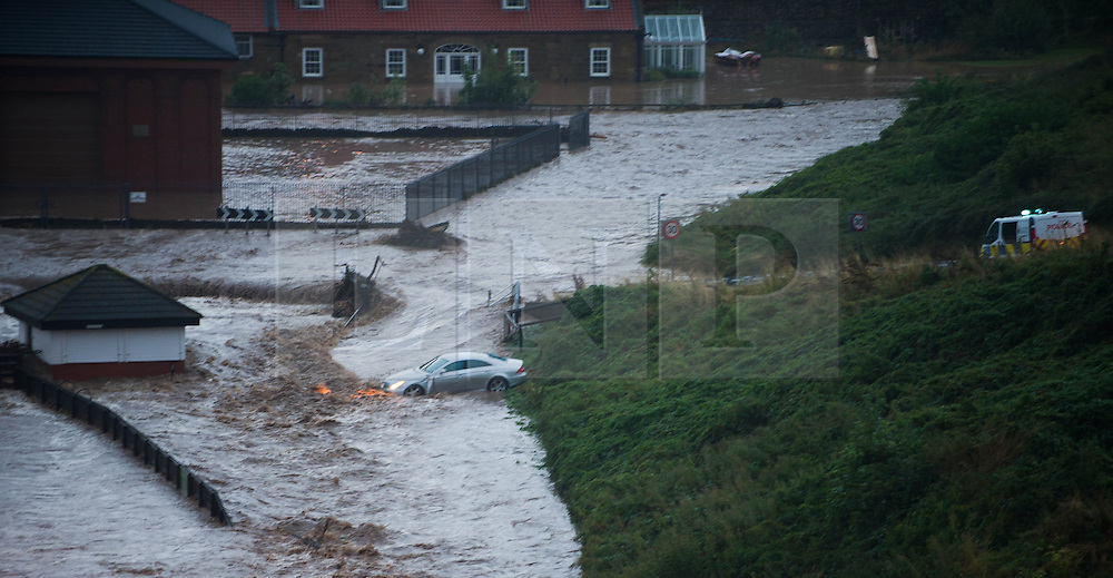 © Licensed to London News Pictures. 06/09/2013<br /> <br /> Saltburn, Cleveland, England<br /> <br /> As darkness falls heavy flooding causes a car to be washed off the road in Saltburn in Cleveland. The driver escaped from the car safely.<br /> <br /> Photo credit : Ian Forsyth/LNP