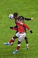 Charlton Athletic forward Omar Bogle (17) and MK Dons' Midfielder David Kasumu (8) battles for possession in header during the EFL Sky Bet League 1 match between Charlton Athletic and Milton Keynes Dons at The Valley, London, England on 2 December 2020.