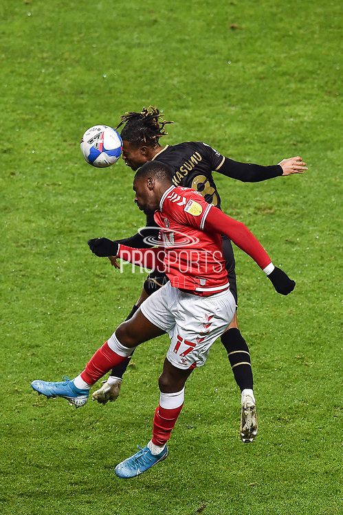 Charlton Athletic forward Omar Bogle (17) and MK Dons' Midfielder David Kasumu (8) battles for possession in header during the EFL Sky Bet League 1 match between Charlton Athletic and Milton Keynes Dons at The Valley, London, England on 2 December 2020.