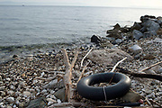 Greece .Lesvos. Rubber ring on the beach. In the distance is Turkey. In 2015 over 200,000 people made th perilous crossing of the Mediterranean from Turkey to Greece with over 2,500 dead or missing. The figure for 2016 is expected to be much higher. Many have crossed on overcrowded inflateable dinghies.