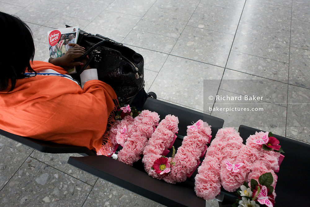 """We look down behind an airline passenger who is alone on seating in the departures concourse of Heathrow Airport's Terminal 5. Mourning the death of a mother, the lady sits with a floral tribute to the recently-deceased relative whose name 'Mum' is laid out next to her in pink flowers. On her lap is the organic Soil Association's magazine Living Earth. Perhaps the woman is on her way to a family funeral and is flying from T5 on this sad flight. Amid the otherwise bustling international airport, the woman seeks solace and tries to sleep before her check-in zone opens. From writer Alain de Botton's book project """"A Week at the Airport: A Heathrow Diary"""" (2009). ."""