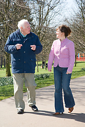Older man and his carer chatting as they walk in the park,