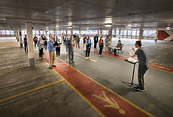 © Licensed to London News Pictures. 23/06/2021. Epsom, UK. Musical Director Julian Collings (R) rehearses Epsom Choral Society in a multi-storey car park in Epsom, Surrey. The choir, in it's 99th year, has resorted to rehearsing in a socially distanced way on the 4th floor of the Ashley Shopping Centre car park after government Covid-19 regulations were updated to say that amateur choirs are only allowed to gather in groups of six indoors. Epsom and Ewell Borough Council agreed to the use of the car park which allows the choral society to rehearse in two groups of 30 outdoors but sheltered from the elements. Photo credit: Peter Macdiarmid/LNP