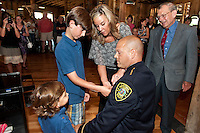 Quinn, Tucker and Tianna Adams get the honors of pinning Laconia's new Police Chief Christopher A. Adams with Chris' dad C. John Adams proudly looking on following the swearing in ceremony at The Freight Room Tuesday afternoon.   (Karen Bobotas/for the Laconia Daily Sun)