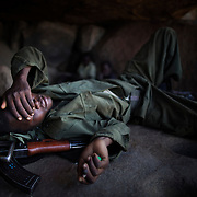 Nader, 19, takes a rest in a mountain cave, before heading to the frontline of Meitan. The soldiers usually sleep outside on thick covers they carry around with them at all time. Sleeping outdoors put them at risk of getting Malaria and getting stung by insects, scorpions or snakes. November 2012