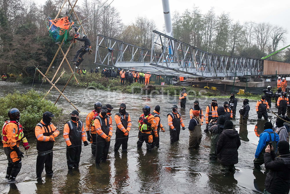 Enforcement agents suspended from a large cherry picker work to remove Dan Hooper, widely known as Swampy during the 1990s, who is sitting on a bamboo tripod positioned in the river Colne on 8th December 2020 in Denham, United Kingdom. The climate and roads activist had occupied the tripod the previous day in order to delay the building of a bridge as part of works for the controversial HS2 high-speed rail link and a large security operation involving officers from at least three police forces, the National Eviction Team and HS2 security guards was put in place to facilitate his removal.