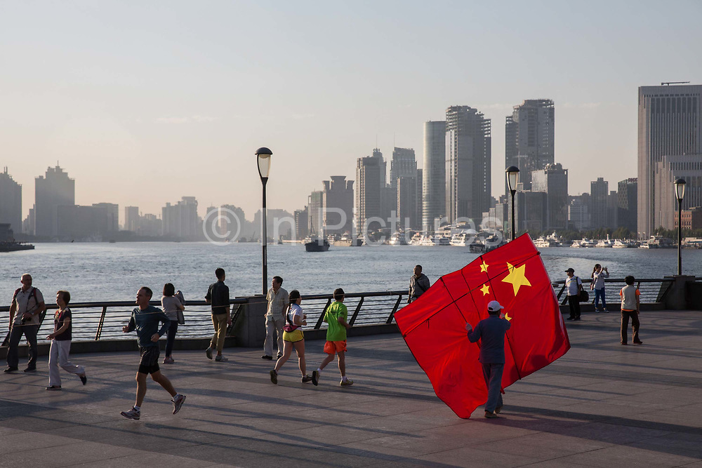 A man carrying a kite in the shape of the Chinese national flag walks along the Bund while buildings of Pudongs Lujiazui financial district stand across the Huangpu River as the sun rises in Shanghai, China, on Friday, Oct. 2, 2015.