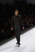 A men's outfit with black trousers and black tone-on-tone double-breasted jacket by Richard Chai at the Spring 2013 Mercedes Benz Fashion Week show in New York.