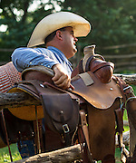 Rylan White grabs a saddle off the rail at Island Ranch in Ames, Oklahoma.