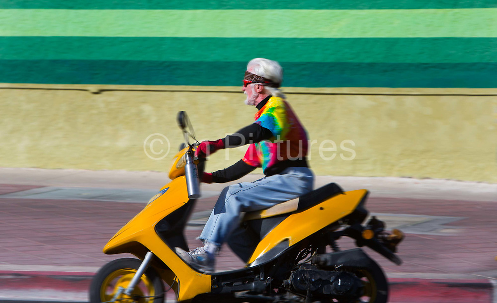 Helmetless elderly man riding a motorcycle in Las Vegas. In Nevada though illegal, many people flout the use of helmets on motorcycles.