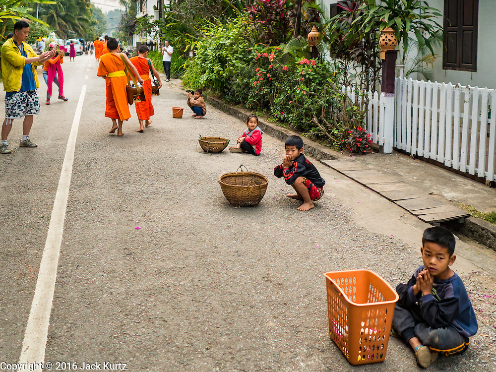 """11 MARCH 2016 - LUANG PRABANG, LAOS: A tourist photographs Buddhist monks during the tak bat while Lao children wait for more monks to pass them. The monks give the children food items they don't use, like candy, that people give to the monks. Luang Prabang was named a UNESCO World Heritage Site in 1995. The move saved the city's colonial architecture but the explosion of mass tourism has taken a toll on the city's soul. According to one recent study, a small plot of land that sold for $8,000 three years ago now goes for $120,000. Many longtime residents are selling their homes and moving to small developments around the city. The old homes are then converted to guesthouses, restaurants and spas. The city is famous for the morning """"tak bat,"""" or monks' morning alms rounds. Every morning hundreds of Buddhist monks come out before dawn and walk in a silent procession through the city accepting alms from residents. Now, most of the people presenting alms to the monks are tourists, since so many Lao people have moved outside of the city center. About 50,000 people are thought to live in the Luang Prabang area, the city received more than 530,000 tourists in 2014.       PHOTO BY JACK KURTZ"""