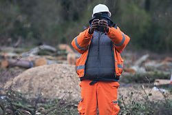 Wendover, UK. 9th April, 2021. A HS2 contractor uses a mobile phone to film a press photographer from a site alongside the A413 where trees have recently been felled for the HS2 high-speed rail link. Tree felling work for the project is now taking place at several locations between Great Missenden and Wendover in the Chilterns AONB, including at Jones Hill Wood.
