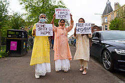 Glasgow, Scotland, UK. 13 May 2021.At approx 5.30 pm police released two men from a Home Office detention vehicle. Accompanied by lawyer Aamer Anwar the men walked to a nearby mosque surrounded by hundreds of police and supporters who had previously been surrounding the vehicle and sitting on the street. Pic; Three female supporters of the two males just released by police. Iain Masterton/Alamy Live News