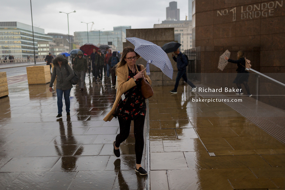 During a spring shower, a lady commuter carrying an umbrella rushes over London Bridge during the evening rush-hour, from the City southwards to Southwark, on 3rd May, in London, England