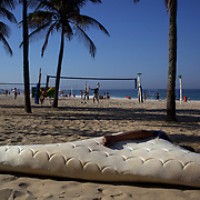 A man sleeps on Ipanema beach as locals play beach volleyball in the background, Rio de Janeiro,  Brazil. 9th July 2010. Photo Tim Clayton..