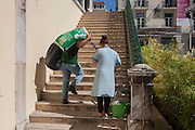 As a cleaner wipes the steps, a workman caries a heavy load up the flight of stairs in Lisbon, Portugal.
