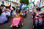 Parade with disabled people in fine costumes on the second day of the Notting Hill Carnival in West London. The Notting Hill Carnival is an annual event which since 1964 has taken place each August, over two days (the August bank holiday Monday and the day beforehand). It is led by members of the West Indian / Caribbrean community, particularly the Trinidadian and Tobagonian British population, many of whom have lived in the area since the 1950s. The carnival has attracted up to 2 million people in the past, making it the second largest street festival in the world. The celebration centres around a parade of floats, dancers and sound systems.
