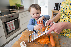 Boy helping his mother to grate carrots in kitchen