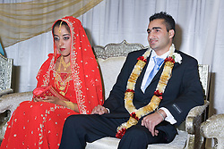 Bride and groom sit together for blessing on their wedding day,