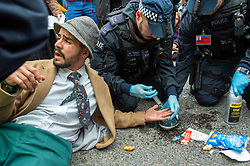 © Licensed to London News Pictures. 10/10/2019. London, UK. Police officers apply chemicals to the hand of an Extinction Rebellion protester after he glued it to the road at the main entrance to London City Airport. Photo credit: Peter Manning/LNP