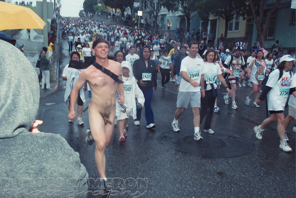 A naked man tries to keep up with his equally naked girlfriend as they descend the Hayes Street hill during the 91st Bay to Breakers Sunday, May 19, 2002 in San Francisco. (Photo by D. Ross Cameron)