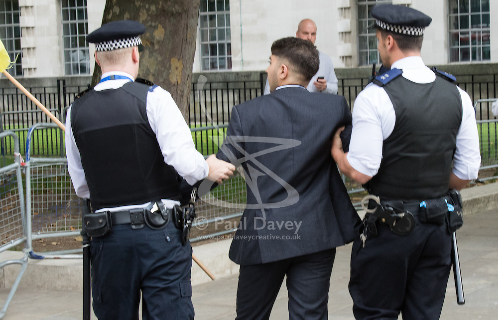 Whitehall, London, September 9th 2015.  A Palestinian supporter is detained by police as pro Palestinian and Israeli counter-protesters clash in Whitehall as the Palestinian Solidarity campaign demands the arrest of Israel's PM Benyamin Netanyahu for war crimes in the 2014 war with Palestinians in Gaza.  // Contact: paul@pauldaveycreative.co.uk Mobile 07966 016 296