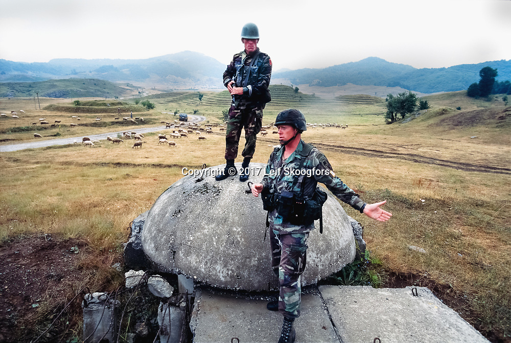 """A US Army Special Operations Officer, assigned to the 173rd Airborne Brigade Combat Team lectures Albanian troops as part of the """"Partnership for Peace"""", the NATO exercise to prepare Albania to join NATO. An Albanian officer stands on a QZ concrete bunker built under the Communist era of dictator Halil Hoxha."""