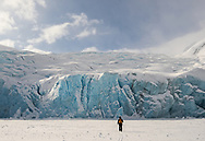 Hiker cross-country skiing to Portage Glacier on Portage Lake in Southcentral Alaska. Winter. Afternoon.