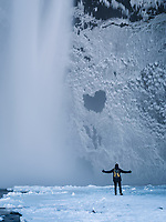 Skógafoss waterfall in winter. Tourist standing by the base of the fall. South Iceland.
