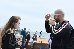 © Licensed to London News Pictures. 17/05/2020. Brighton, UK. A couple drink a beer as they wear protective face masks on the seafront at Brighton. Some lockdown rules have been relaxed to allow people to travel further to exercise and to sunbathe.  Photo credit: Liz Pearce/LNP