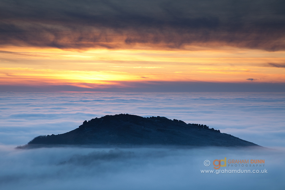Hen Cloud's summit is just visible above a spectacular temperature inversion at dusk in the southwestern Peak District. A sunset landscape scene in Staffordshire, England, UK.