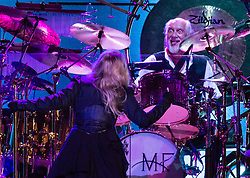 © Licensed to London News Pictures. 27/05/2015. London, UK.   Mick Fleetwood playfully pokes his young out at Stevie Nicks as Fleetwood Mac perform live at The O2 Arena, together with Christine Mc Vie who has rejoined the band.   The band are due to headline the Isle of Wight Festival next month. Fleetwood Mac are a British-American rock band consisting of members Mick Fleetwood (drums), John McVie (bass guitar), Christine McVie (keyboards/vocals), Lindsey Buckingham (guitars, vocals), Stevie Nicks (vocals, tambourine).  Photo credit : Richard Isaac/LNP