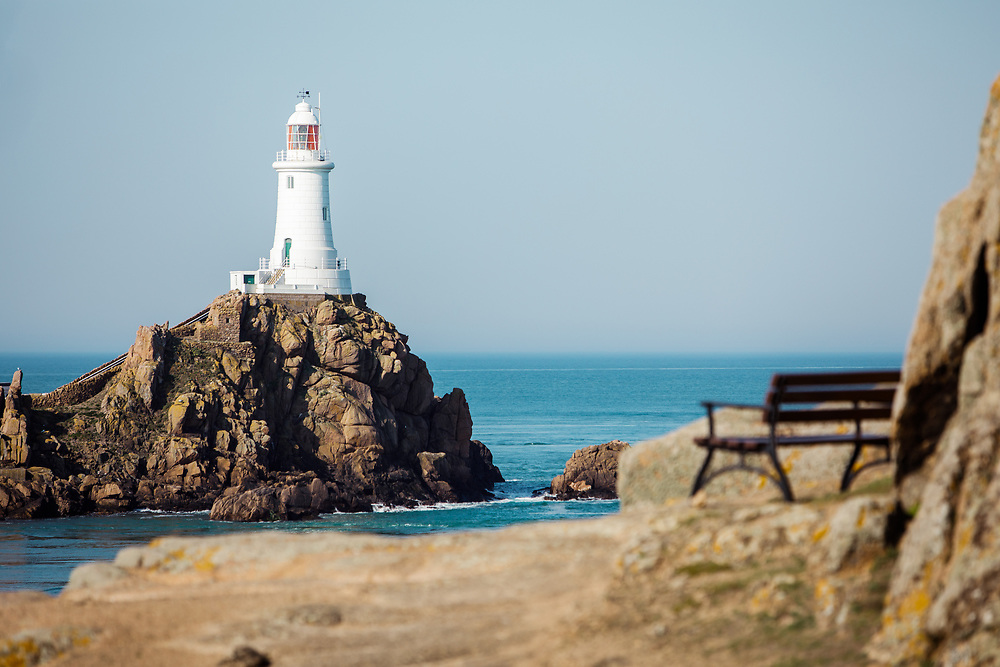Bench with a view straight out at the popular tourist attraction and landmark, Corbiere lighthouse, surrounded by calm blue sea on a sunny day in summer in Jersey, Channel Islands
