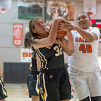 Hailey Long (40) of Gallup gets tangled up with Karina Segura (32) of St. Pius X under the basket as the fight for the rebound in Gallup on Wednesday. St. Pius won 53-43.