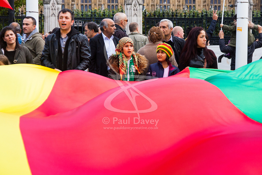 London, October 11th 2014. Thousands of protesters from the UK's Kurdish community demonstrate in London against the delay in assisting the people of the Syrian city of Kobane in their fight against ISIS. They also accuse Turkey, with whom the Kurds have had a long-running insurgency of siding with the Islamic State by doing nothing to help Kurds in Kobane. PICTURED:  A giant flag billows as women and children chant slogans