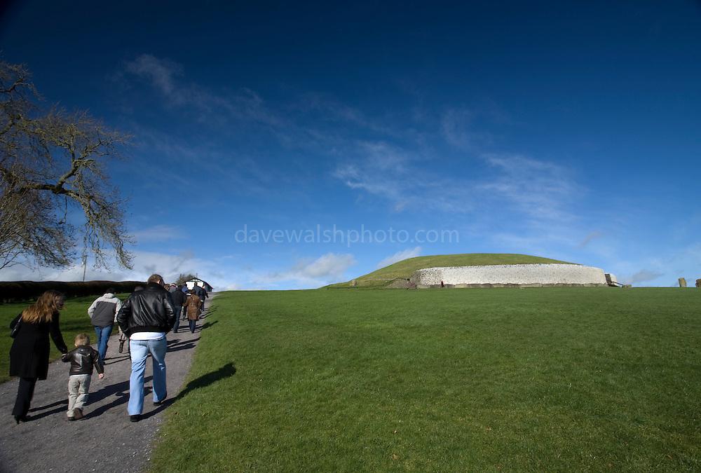 Tourists walking towards Newgrange passage grave, County Meath, Ireland.