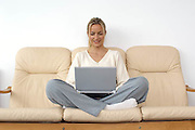 women with a laptop computer sitting crossed legged on a sofa<br />