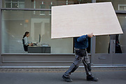 An obscured workman manhandles a wooden board sheeting past an business receptionist, on 5th March 2019, in London, England.
