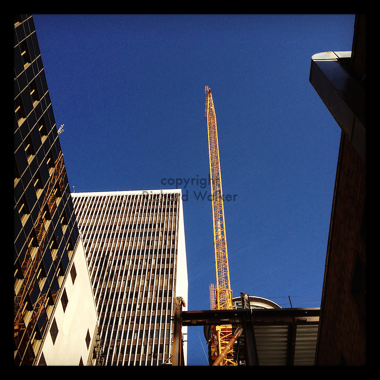 2012 MAY 10 - A construction crane rises against a blue sky in downtown Seattle, WA, USA. Taken with Apple iPhone using Instagram App. By Richard Walker
