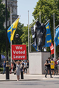 A woman holds a huge sign with the words We Voted Leave at Parliament Square on the 23rd July 2019 in London in the United Kingdom.