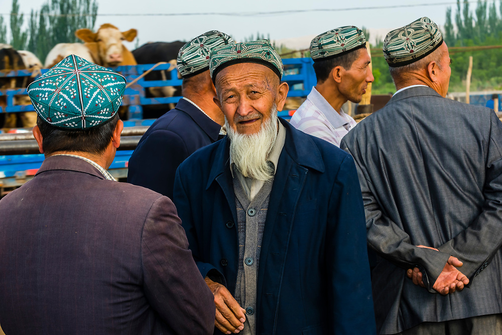 Uyghur men at the Sunday Livestock market just outside Kashgar (China's westernmost city), Xinjiang Province, China. Kashgar is along the Silk Road, near Tajikistan and Pakistan. Uyghur people are a Central Asian people of Muslim Turkic origin.