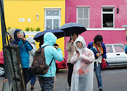 Cape Town - 180629 - A group of tourist dressed in rain gear visits the colourful Bo-Kaap. While the rain started pouring in Cape Town on Friday, the SA Weather Service has warned that an intense cold front is expected to land on Sunday and continue into Monday. Picture: Henk Kruger/ANA/African News Agency